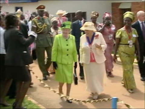 queen visit to aids clinic in kampala; queen along and woman towards as ugandan people make high-pitched cheers and wave flags and men perform tribal... - kampala stock-videos und b-roll-filmmaterial