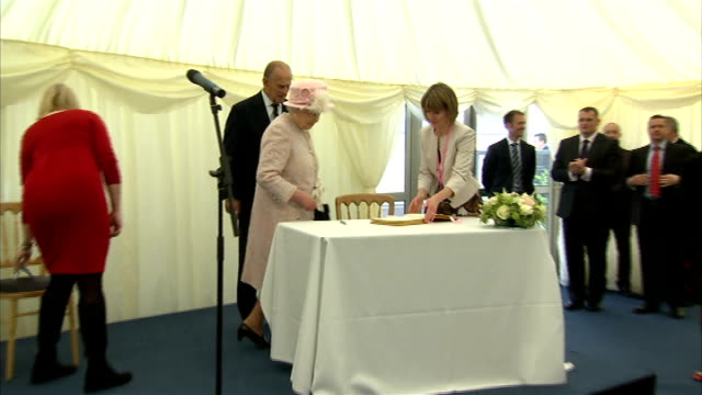queen visit to rosie maternity centre cambridge queen unveiling plaque / queen signing book / children presenting flowers to queen queen leaving /... - book signing stock videos & royalty-free footage