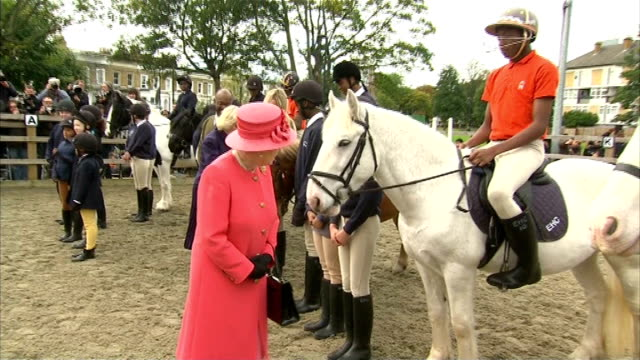 london brixton ebony horse club ext queen elizabeth ii and camilla duchess of cambridge along towards horses camilla feeding horse mints queen along... - ニナ・ホサイン点の映像素材/bロール