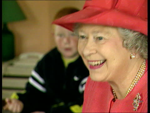 Glasgow Queen Elizabeth II sitting down at table of McCarron family during visit to housing estate CMS Queen MS Queen at table as woman asks her how...