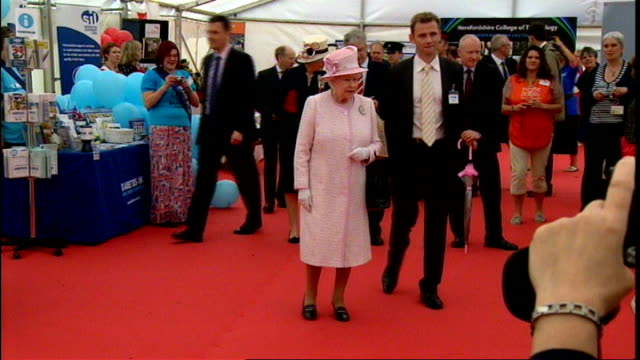 queen visits herefordshire; queen looking at exhibits in marquee / man whittling wood / queen leaving marquee to cheers from crowd / queen along... - herefordshire bildbanksvideor och videomaterial från bakom kulisserna