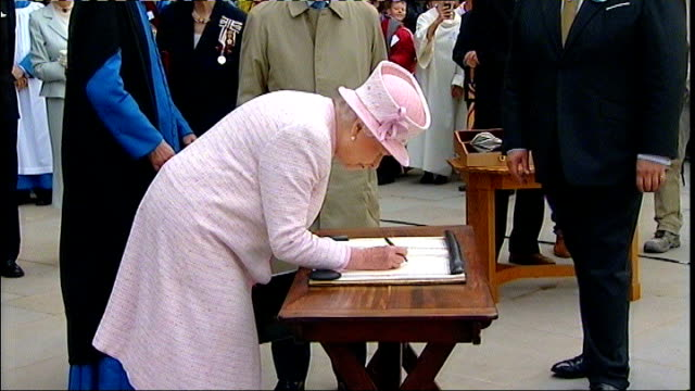 queen visits herefordshire; queen receiving flowers on walkabout / covered area outside cathedral and queen and prince philip signing cathedral... - herefordshire stock videos & royalty-free footage