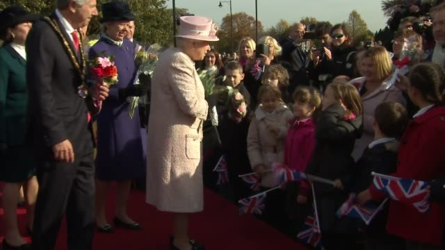 queen visits newmarket england suffolk newmarket ext queen elizabeth ii along given flowers by children tracking shot along road past crowds waving... - newmarket suffolk england stock videos and b-roll footage