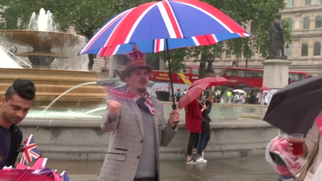 queen's 90th birthday: people in trafalgar sq celebrating in the rain; ladies in wigs seated at table, drinking in the rain / various of people in... - garnish stock videos & royalty-free footage