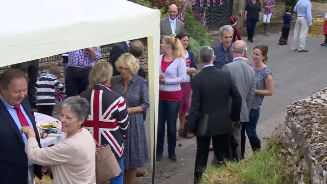 Queen's 90th birthday Prince Charles and Camilla attend Patron's Lunch Camilla Duchess of Cornwall chatting to locals / views of stone wall marquee...