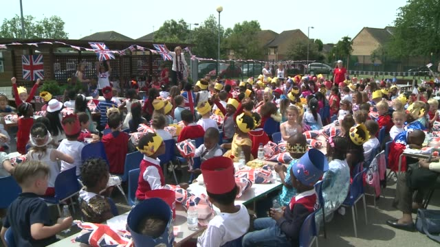 queen's 90th birthday: service of national thanksgiving held; essex: dagenham: schoolchildren seated at 'strete party' in school playground young boy... - 90th birthday stock videos & royalty-free footage