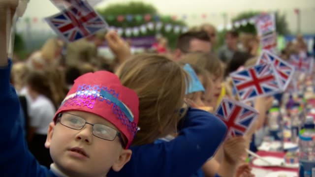 queen's 90th birthday service of national thanksgiving held greater manchester bolton ext schoolchildren waving union jack flags at street party... - bolton greater manchester stock videos and b-roll footage