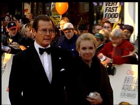queens birthday honours list; lib london: ext cms sir roger moore and wife along - 俳優 ロジャー・ムーア点の映像素材/bロール