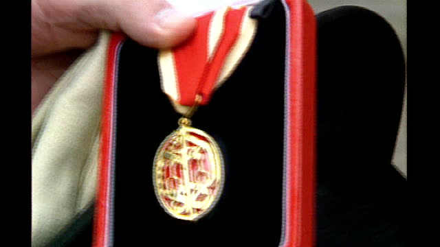 queen's birthday honours list: recipients announced; t04039310 1993 location unknown: ext british empire medal in box mbe medal held - 光栄点の映像素材/bロール
