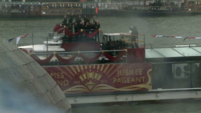 queen's diamond jubilee beacons lit around the world 362012 various of boats along river thames during river pageant people wearing raincoats in... - bandstand stock videos and b-roll footage