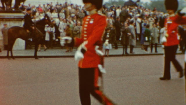 queen's guard at buckingham palace ' marching parade / trooping the colour at buckingham palace on june 05, 1962 in london, england - 軍旗分列行進式点の映像素材/bロール