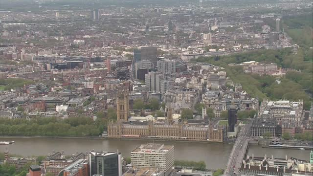 aerials of prince charles' and the queen's journeys to parliament; england: london: westminster: ext air view houses of parliament, union jack flag... - politics stock videos & royalty-free footage