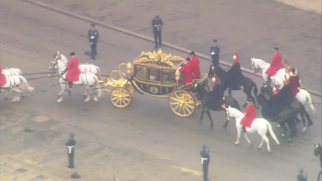 queen's speech carriage procession queen's carriage and procession along though horse guards parade and onto whitehall / along through parliament... - the queen's speech state opening of uk parliament stock-videos und b-roll-filmmaterial
