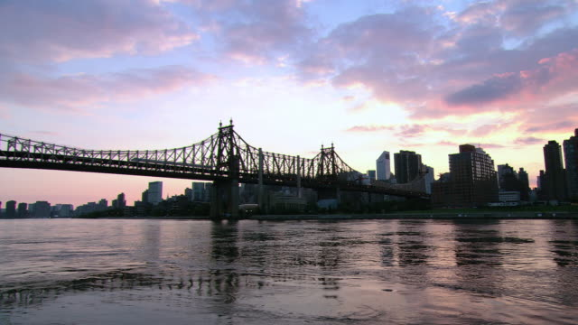 pan queensboro bridge over the glistening east river at sunset / new york city, new york, united states - east river stock videos & royalty-free footage