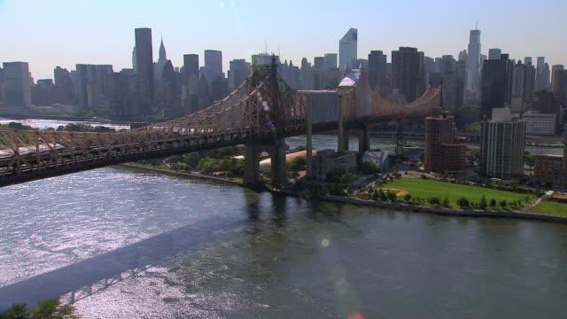 vidéos et rushes de aerial queensboro bridge passing over roosevelt island and east river / new york city, new york, united states - format vignette