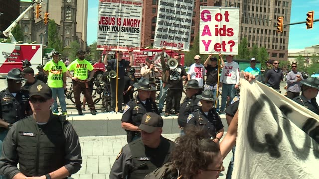 wgn 'queers against racism' group and a jewish boy stand in front of a antigay antiislam 'christian' group at cleveland's public square near the 2016... - ホモフォビア点の映像素材/bロール