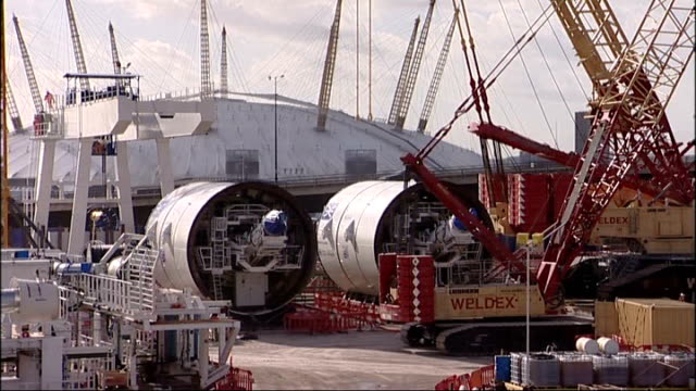 questions over safety after worker injured on crossrail site tx tunnel boring machines and other construction eqipment with o2 arena in background... - クロスレール路線点の映像素材/bロール