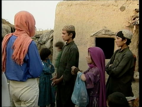 Quetta EXT SEQ Afghan refugee children in refugee camp Fifteen year old refugee standing speaking to Moore with brothers sisters beside BV Children...