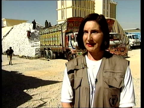 quetta gv lorry of wheat sacks next large pyramid shaped stack as aid workers unloading wheat sacks mss aid workers unloading sacks of wheat from... - burka stock videos and b-roll footage