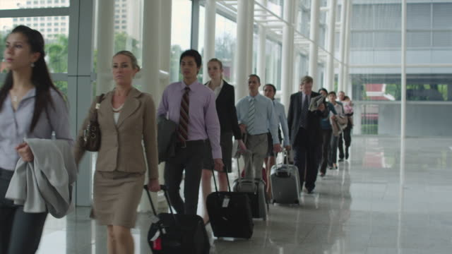 MS TD Queue of business people pulling suitcases walking through office lobby, Bangkok, Thailand