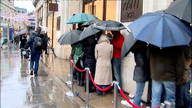 queues form for jimmy choo shoes; england: london: regent street: ext / raining queues outside h&m store speeded up tracking shot vox pops people... - cut video transition stock videos & royalty-free footage