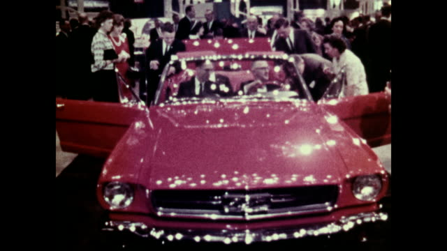 vídeos de stock e filmes b-roll de /quick montage of ford dealers and their wives attending a preview event for the brand new 1965 ford mustang 1965 ford mustang dealer preview on may... - 1964