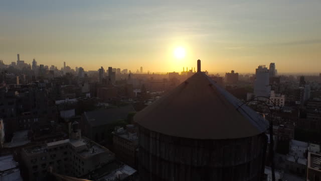 Quick pan up over water towers in Soho toward bright orange sun rising over New York City