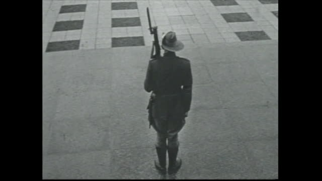 quick shot exterior shrine of remembrance / soldier stands to attention - with bayonet rifle over shoulder and wearing slouch hat - seen from rear -... - bayonet stock videos & royalty-free footage