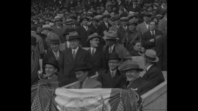 Quick shot looking down on packed stands at Polo Grounds silhouettes of spectators in fg / title card Manager McGraw and New York's pennant chasers /...