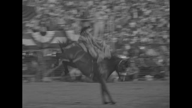 Quick shot of waving Leo Carrillo on horseback at Los Angeles Memorial Coliseum / banner Paramount Riders Inc with large crowd of spectators / Roy...