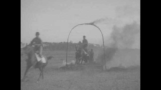 "quick shot title card: ""filipino cavalrymen ride through flames - manila - rough riding horsemen perform daring feats in snappy maneuvers"" / filipino... - trough stock videos & royalty-free footage"