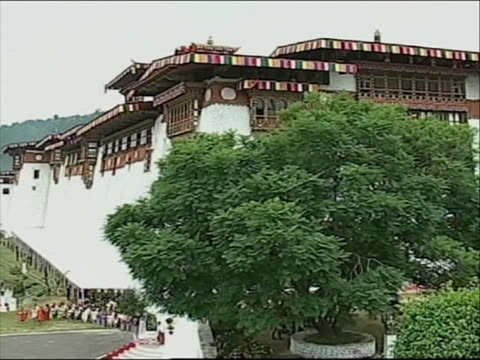 quick shots of exteriors of bhutan castle first one has castle to the right with the pond in view, second shot is outside the castle with green trees... - religious dress stock videos & royalty-free footage