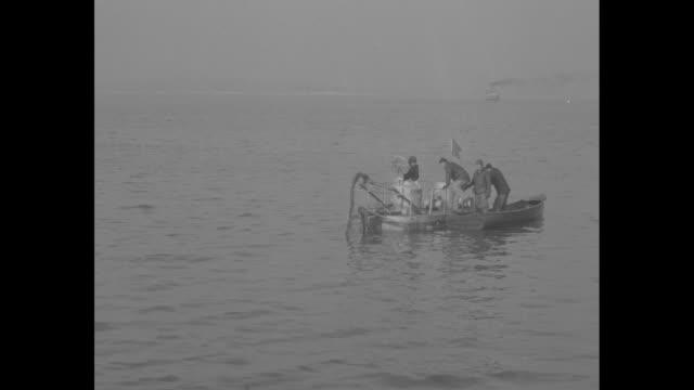 vídeos y material grabado en eventos de stock de quick shots submarine launch into water from dock, towed behind boat / dr. william beebe climbs into sub through conning tower / it submerges / men... - salir del agua