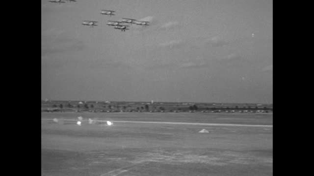 """vidéos et rushes de """"flying high wide and handsome"""" / an aerial view of thousands of spectators; planes take off, fly over and they form two parallel lines in the sky /... - biplan"""