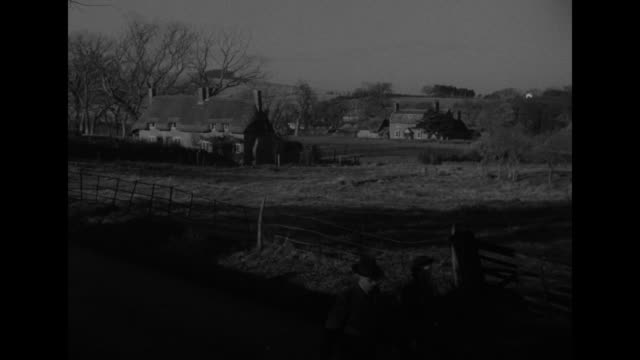 shall letcombe bassett die / woman opens gate at thatched house / people walking briskly past fenced meadow / woman with bicycle exits house through... - strohdach stock-videos und b-roll-filmmaterial