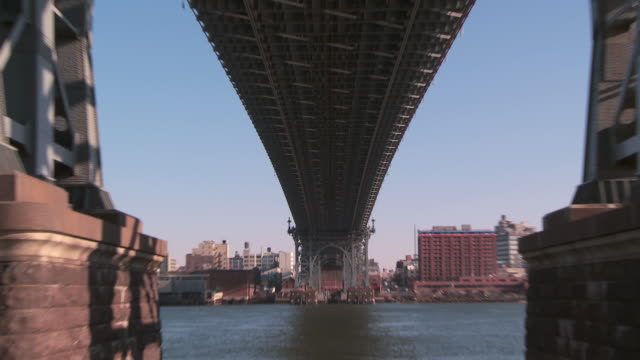 vídeos de stock e filmes b-roll de quick zoom out reveal from beneath the williamsburg bridge stretching out across the east river into brooklyn at mid day - meio dia