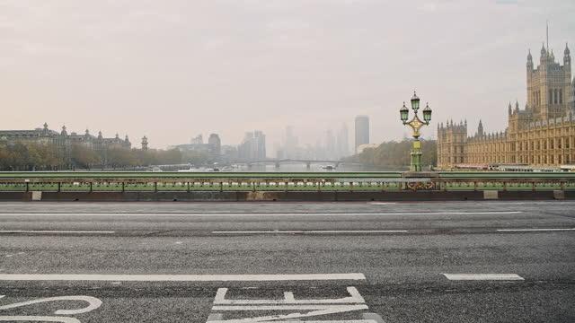 quiet, empty and deserted roads and streets in london in coronavirus covid-19 lockdown at westminster bridge during the global virus pandemic, with no people at rush hour - internationell sevärdhet bildbanksvideor och videomaterial från bakom kulisserna
