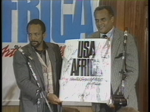 "quincy jones and harry belafonte hold up a sign that reads usa africa around the time that the hit charity single ""we are the world"" was released. - willie nelson stock-videos und b-roll-filmmaterial"