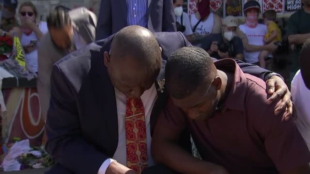vidéos et rushes de quincy mason, son of george floyd, kneels with family attorney ben crump at the site of george floyd's death in minneapolis, minnesota. - respect