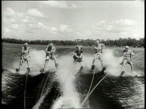 a quintet of costumed water skiers perform various stunts / close up of skis in the water / water skiers attempt to jump on water ramp / water skiers... - crisscross stock videos & royalty-free footage