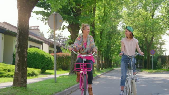 vídeos y material grabado en eventos de stock de slo mo ts quirky madre y su hija montando bicicletas en la calle y riendo - familia con un hijo