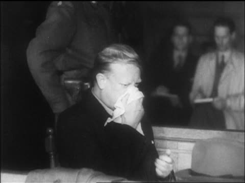 quisling blowing nose in courtroom during war crimes trial / newsreel - war crimes trial stock videos and b-roll footage