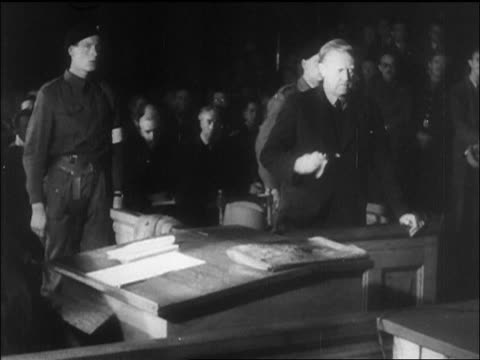 quisling standing wiping face in courtroom during war crimes trial / newsreel - war crimes trial stock videos and b-roll footage