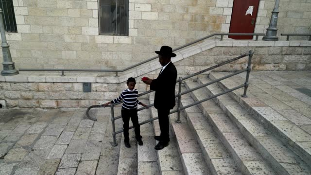 A Rabbi and his son prepare to walk to the Wailing Wall