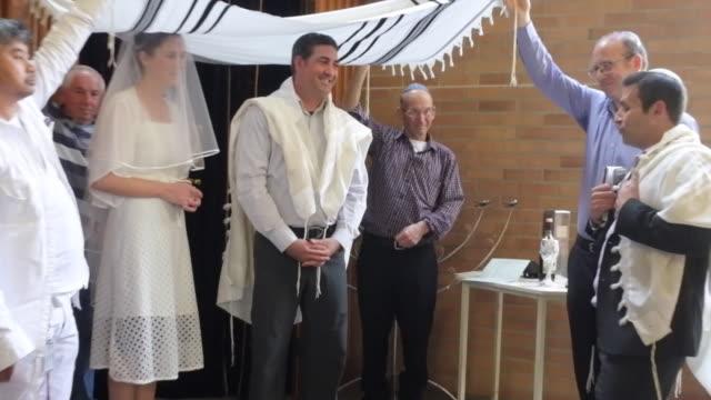 Rabbi Blessing Jewish Bride and Bridegroom in Orthodox Jewish Wedding Ceremony