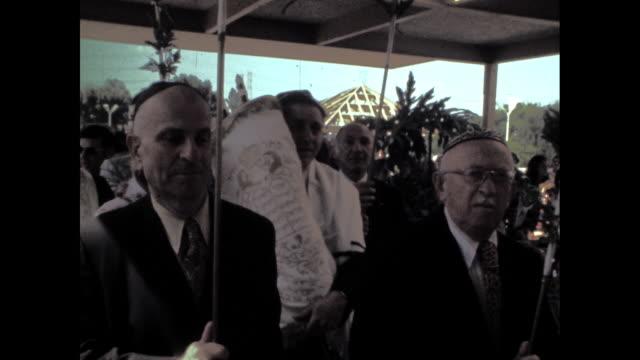 vídeos y material grabado en eventos de stock de rabbi carrying torah under a canopy help up by four men through crowd of people. - torah