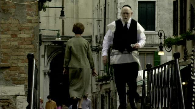 a rabbi strolls past other pedestrians in a venice ghetto. available in hd. - ghetto video stock e b–roll