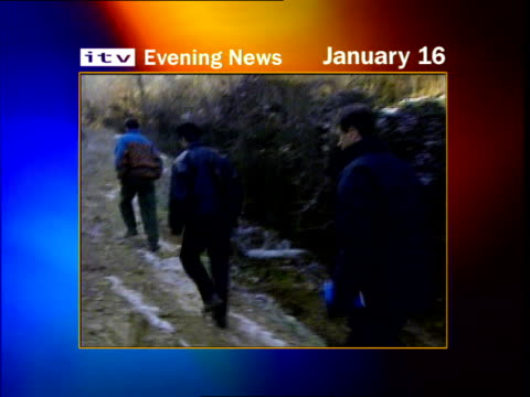 Racak massacre LIB Serbia Kosovo Bill Neely and men along track thru mountains Body of murdered Kosovo Albanian covered by blanket Neely and otherrs...