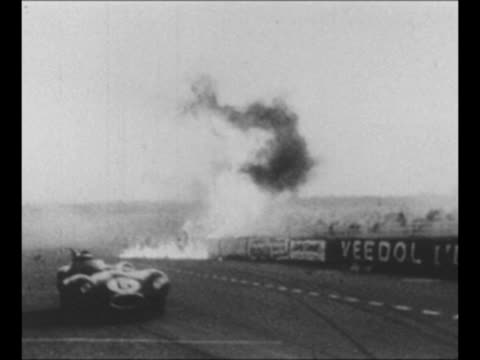 race car approaches passes during french grand prix race / spectators lean over wall in stands / race car hits wall fiery car parts soar into stands... - 1955 stock-videos und b-roll-filmmaterial