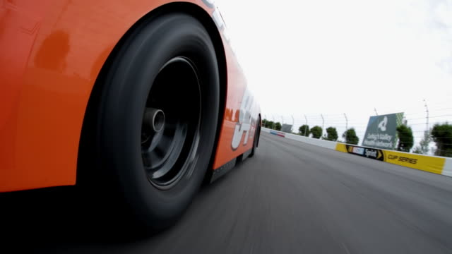 race car pov as orange stock car gains on and passes white car in the curve to take the lead. - tyre stock videos & royalty-free footage